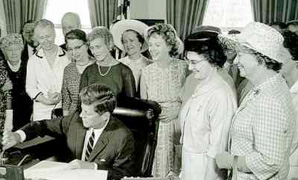 President John F. Kennedy signs the 1963 Equal Pay Act into law as 1962-63 BPW/USA president Dr. Minnie Miles watches. Dr. Miles received the first pen from the signing.